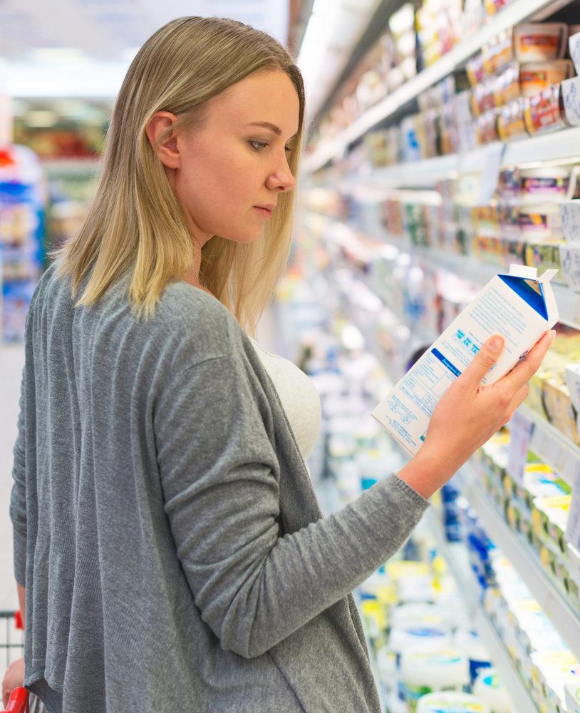 woman-choosing-milk-in-grocery-store
