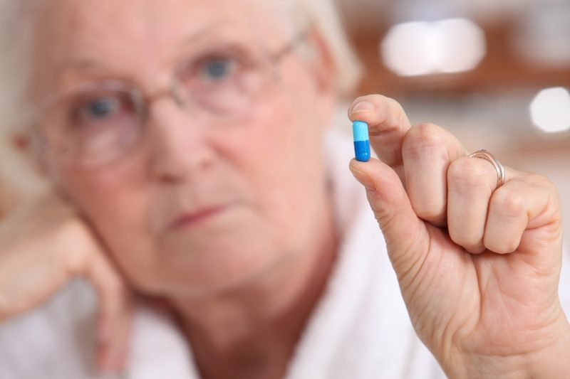 elderly-woman-holding-a-capsule-between-her-fingers