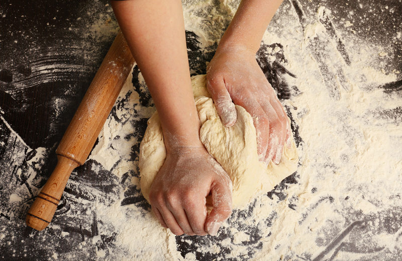 making-dough-by-female-hands-on-wooden-table-background