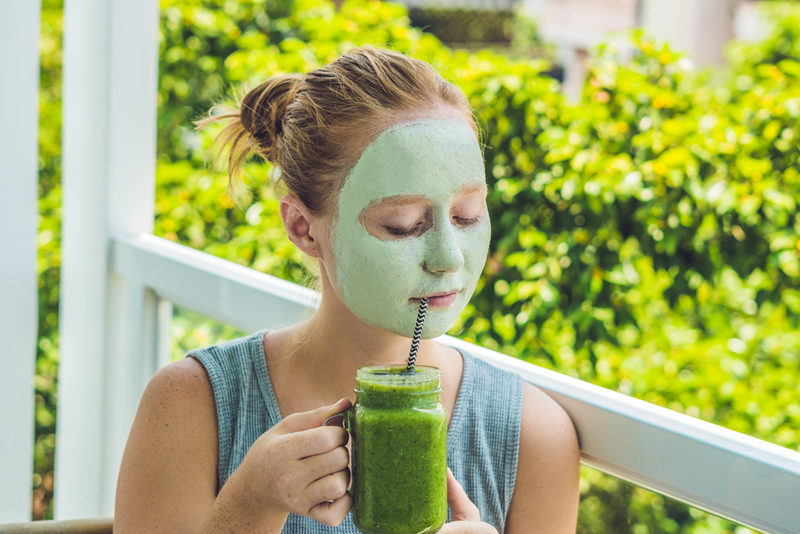spa-woman-applying-facial-green-clay-mask-beauty-treatments-fresh-green-smoothie-with-banana-and-spinach-with-heart-of-sesame-seeds-love-for-a-healthy-raw-food-concept-detox-concept
