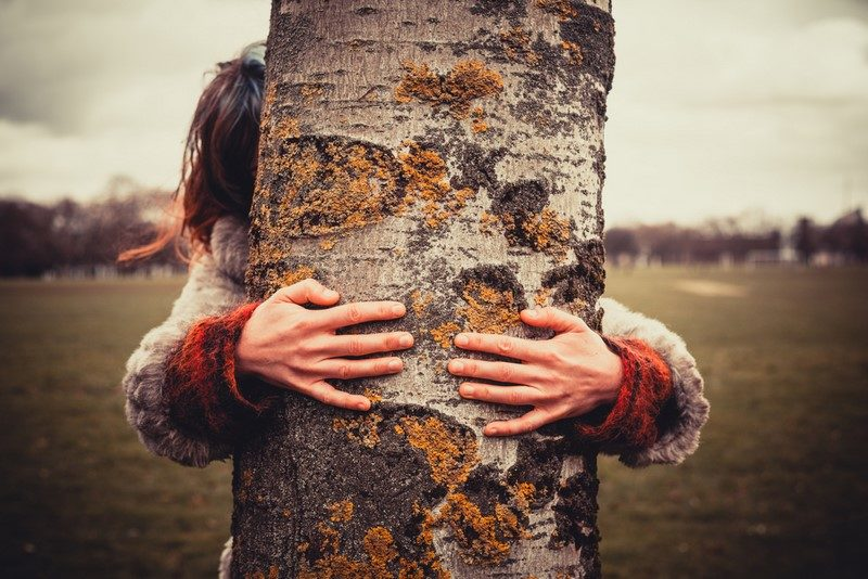 young-woman-is-in-the-park-on-a-winters-day-and-is-hugging-a-tree