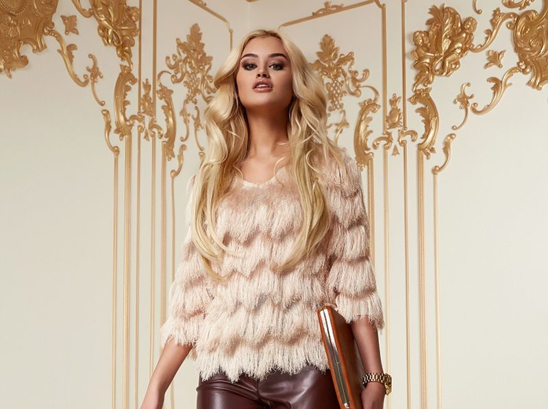 beautiful-young-sexy-woman-with-long-blonde-curly-hair-thin-slender-with-evening-make-up-wearing-a-tight-leather-pants-pink-blouse-patent-leather-high-heeled-shoes-in-hand-holding-bags-clutches-party