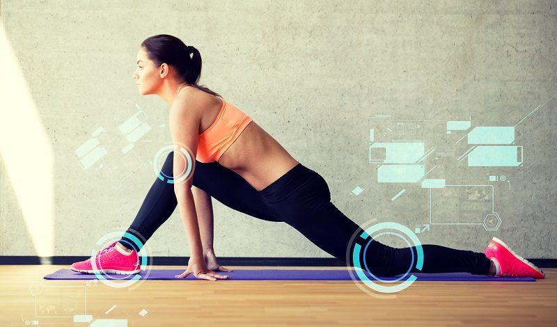 smiling-woman-stretching-leg-on-mat-in-gym