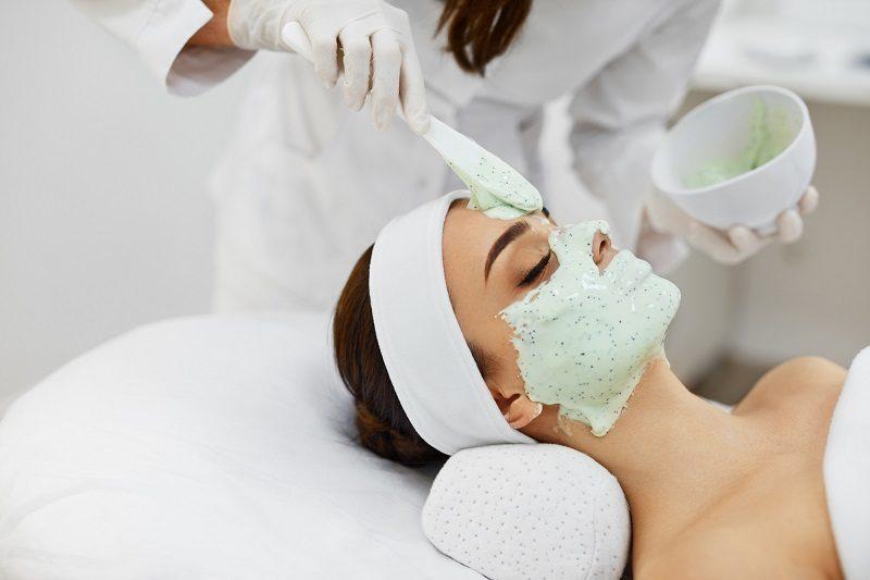 facial-skin-care-beautiful-woman-getting-cosmetic-mask-in-salon