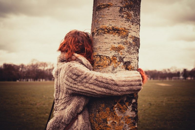 young-woman-is-in-the-park-on-a-winters-day-and-is-hugging-a-tree-2