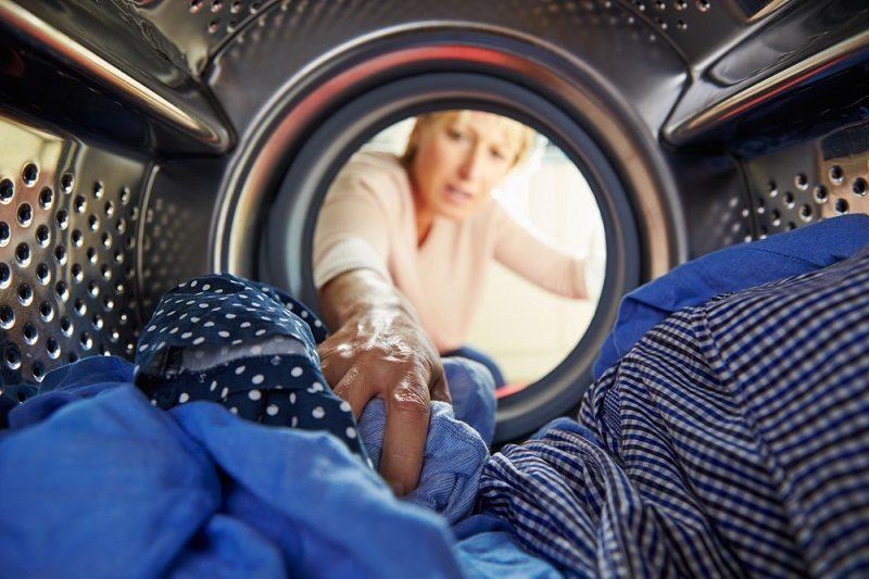 woman-doing-laundry-reaching-inside-washing-machine