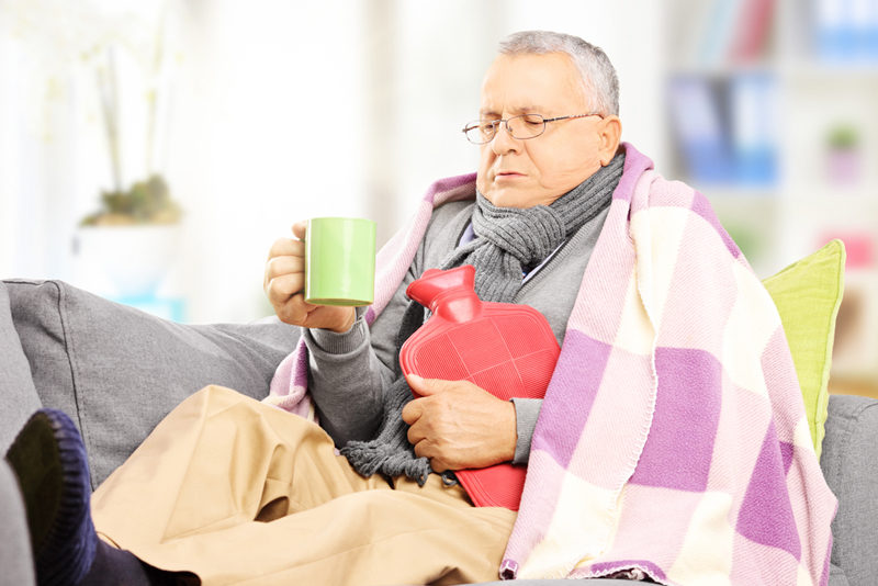 ill-man-on-a-sofa-covered-with-blanket-drinking-hot-tea-at-home