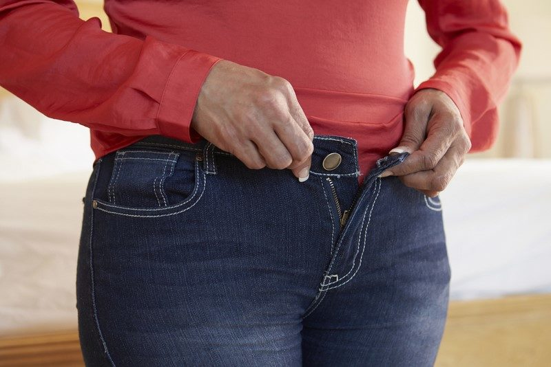 close-up-of-overweight-woman-trying-to-fasten-trousers