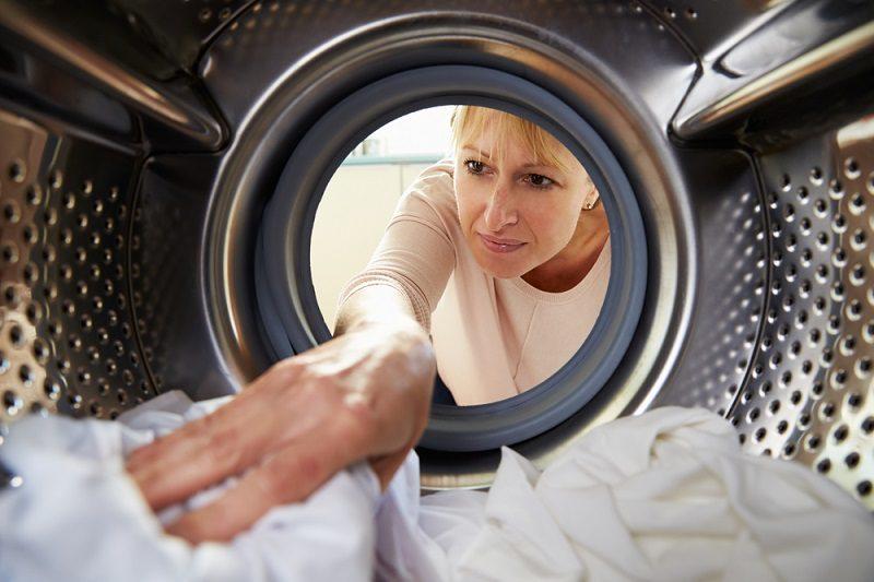 woman-doing-laundry-reaching-inside-washing-machine-2