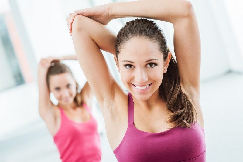young-women-at-the-gym-sitting-on-a-mat-and-doing-stretching-exercises-for-arms