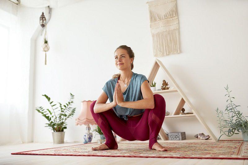 young-woman-doing-garland-pose-at-yoga-studio