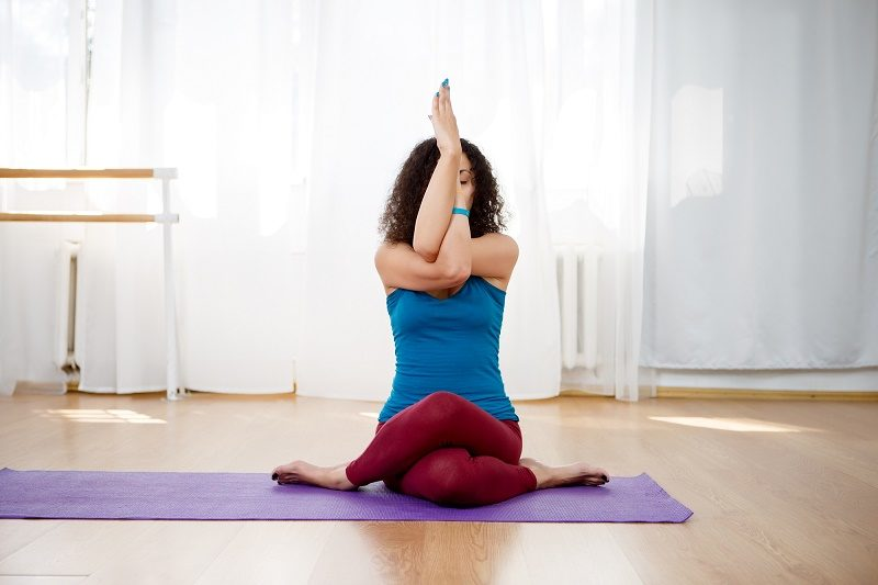 brunette-woman-practicing-eagle-pose-in-yoga-class