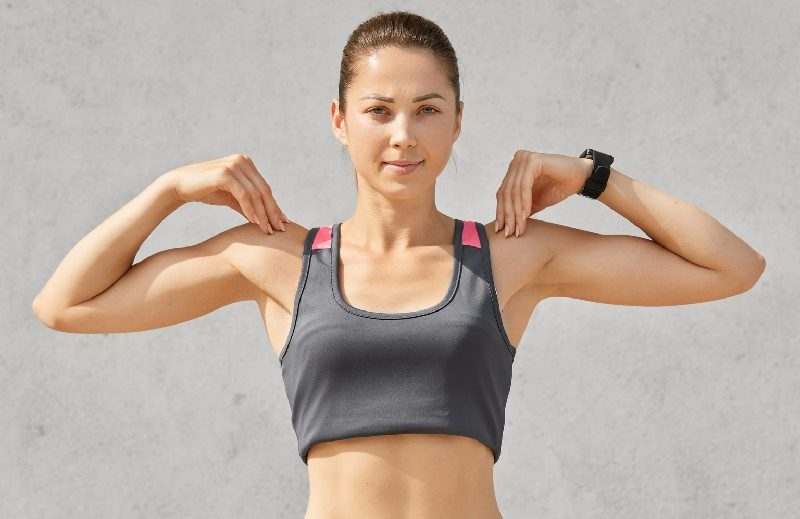 waist-up-shot-of-sporty-woman-keeps-both-hands-on-shoulders-does-exercises-during-morning-workout-wears-casual-top-and-leggings-looks-directly-seriously-at-camera-isolated-over-grey-background