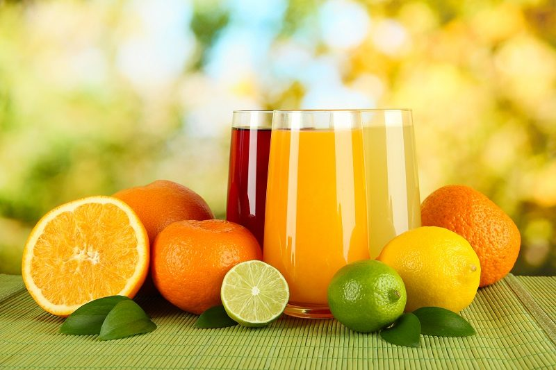 glasses-of-juise-with-leafs-and-fruits-on-table-on-bright-background
