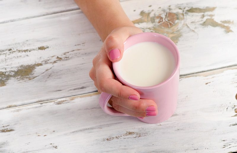 womans-hand-holding-cup-of-yogurt