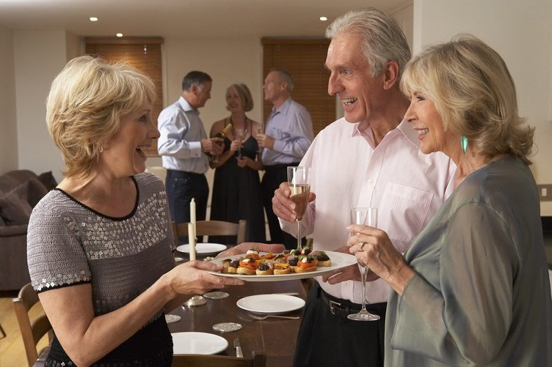 woman-serving-hors-doeuvres-to-her-guests-at-a-dinner-party