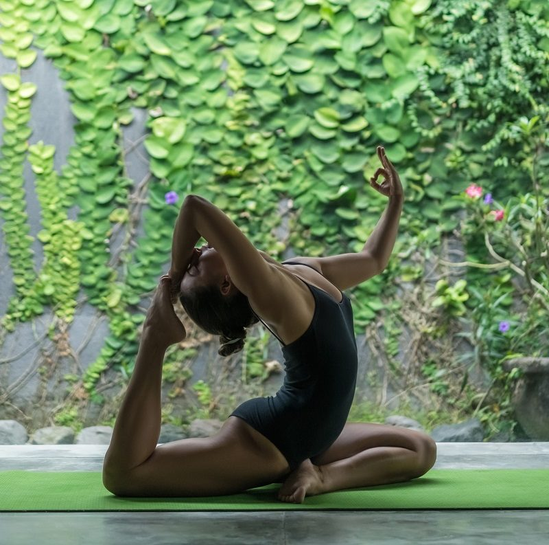side-view-of-beautiful-young-woman-practicing-yoga-in-one-legged-king-pigeon-pose-eka-pada-rajakapotasana-on-terrace-in-front-of-wall-covered-with-green-leaves