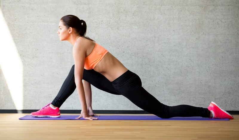 smiling-woman-stretching-leg-on-mat-in-gym-2