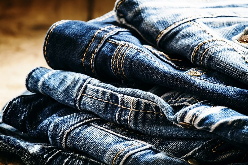 classic-casual-blue-jeans-pile-on-a-vintage-wooden-background