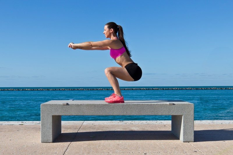 hispanic-woman-doing-squats-on-a-bench-by-the-ocean