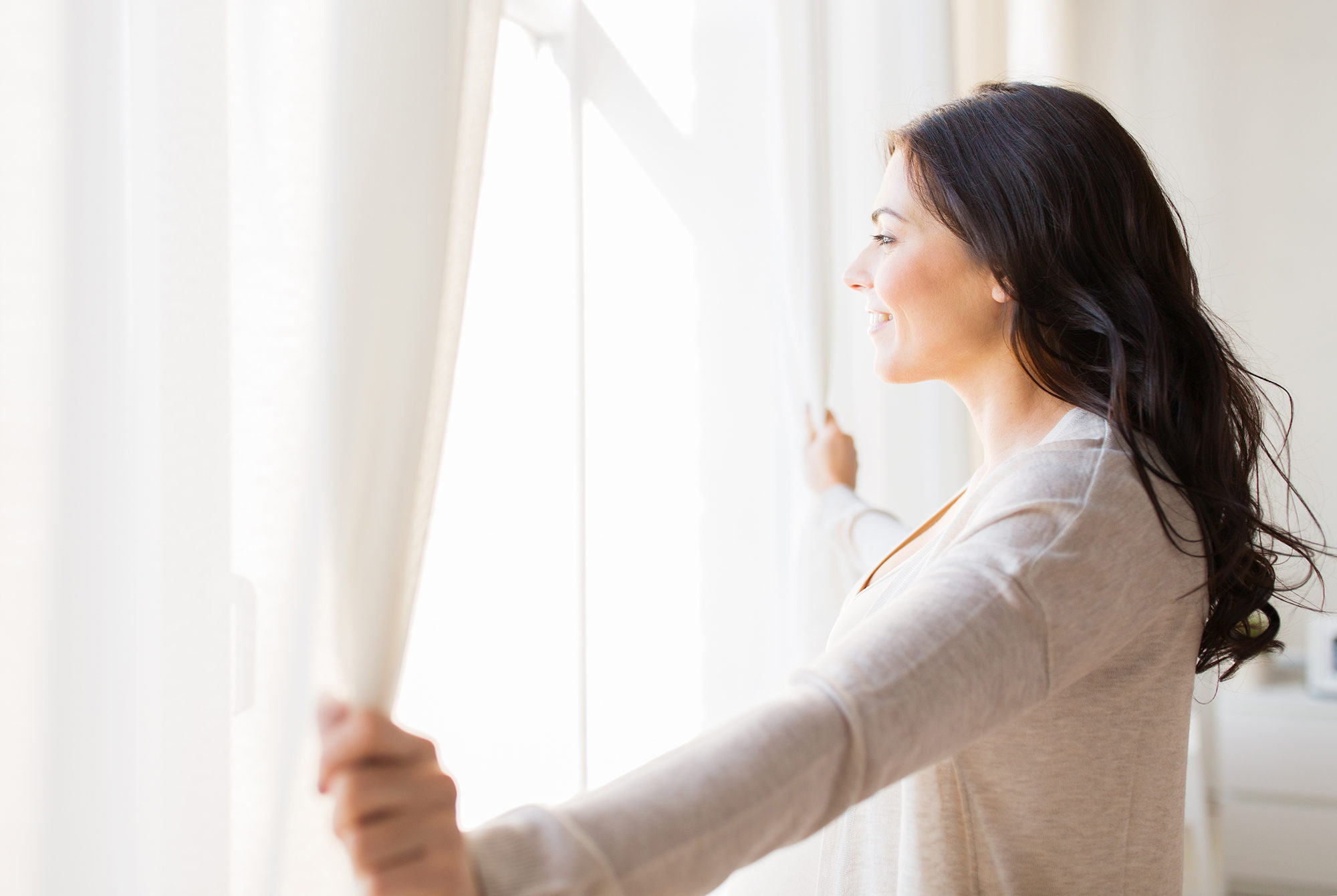 close-up-of-woman-opening-window-curtains